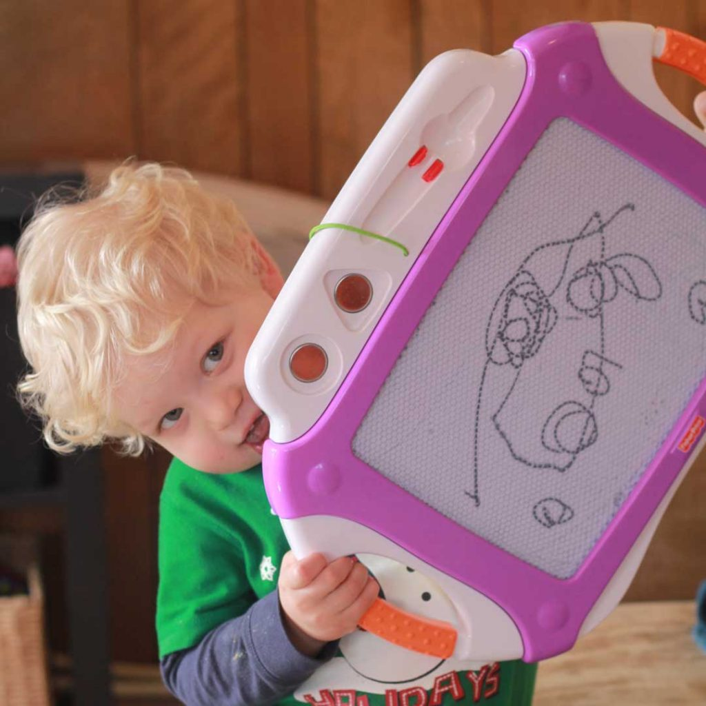 Toddler displaying his art work: Whether my kids are two or twelve I want to be at home with them where my heart is happiest.